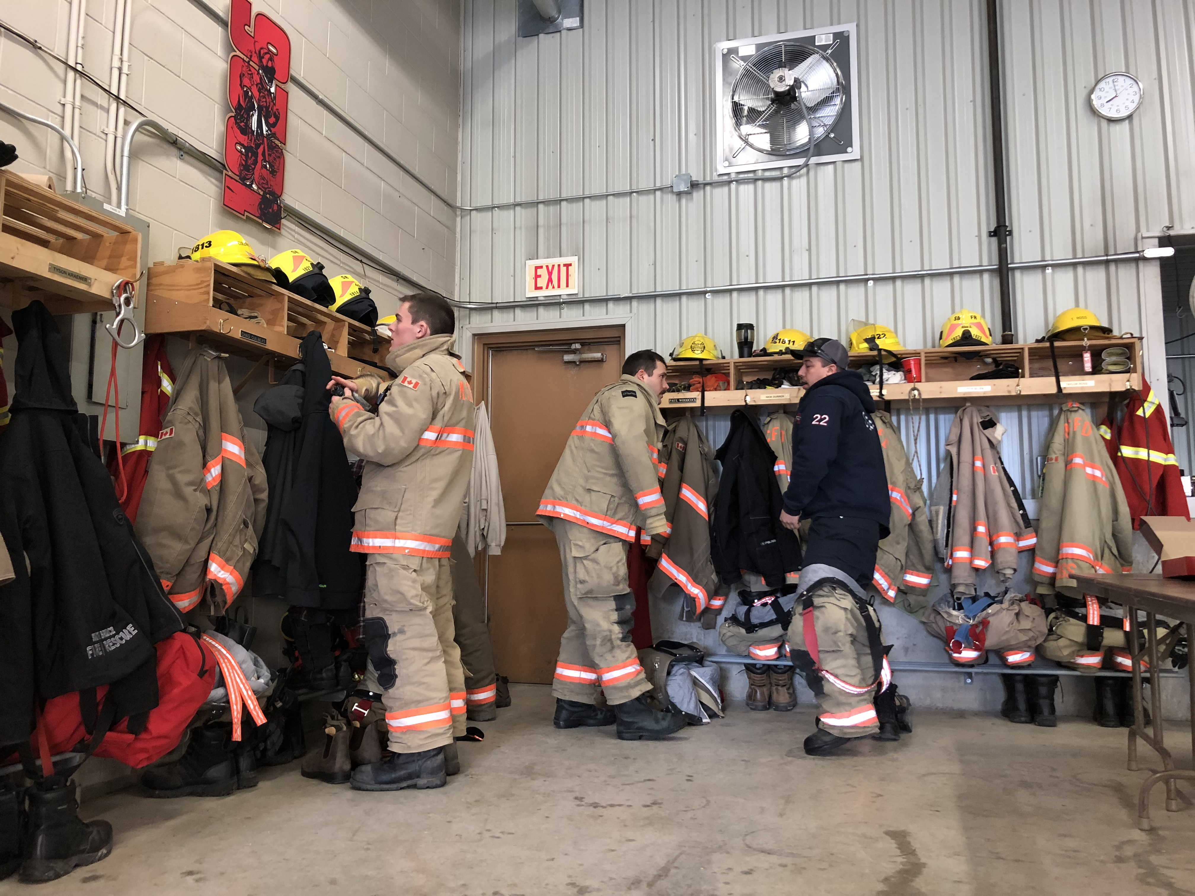 firefighters putting on protective gear in a fire station