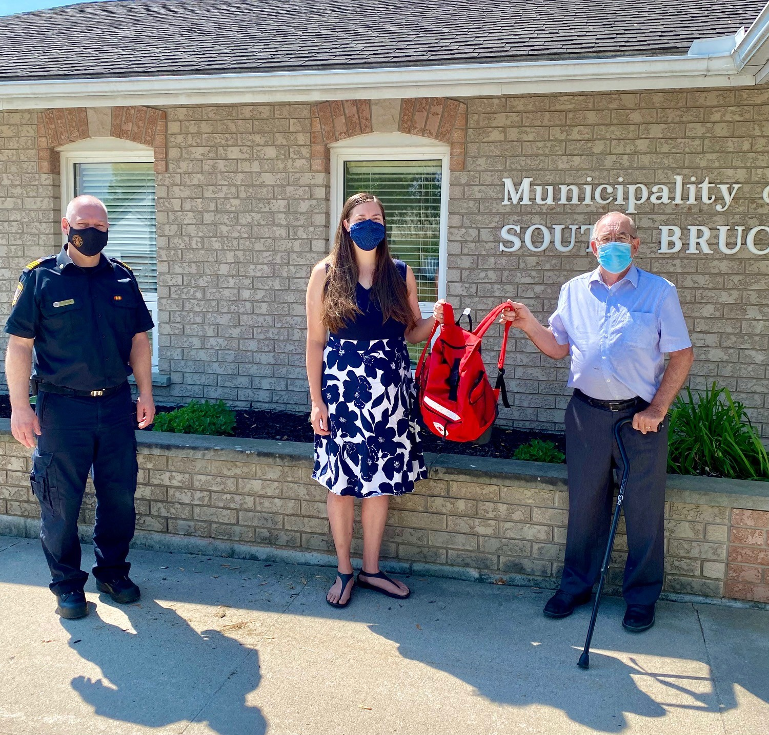 Pictured is Chief Gallant, Hilory Murphy, and Mayor Buckle, presenting a red emergency kit